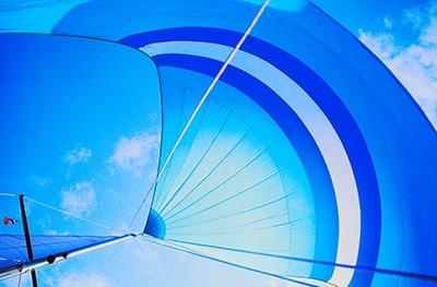 Beitragsbild zu Leistungen - Unterschiedliche Schöne Bilder - Blaues Spinnaker Segel voll im Wind vor blauem Himmel aus der Froschperspektive fotografiert.