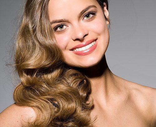 Sedcard EXTENDED 4.1 Portrait von Carina, lange lockige Haare mit Seitenscheitel, ein glückliches Lächeln mit trägerlosem schwarzen Top.