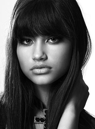 Beauty Shooting mit Hevelin - Schwarzweiss Beauty Foto eines jungen Mädchens mit Blick zur Kamera und Hand in den Haaren. Um den Hals trägt Hevelin ein grosses Kreuz.