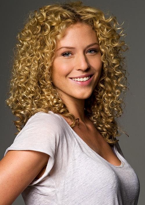 Sedcard Shooting zur Sedcard EXTENDED6 - ein blondes, gelocktes strahlendes Mädchen im Portrait, im hellen T-Shirt mit Ausschnitt.