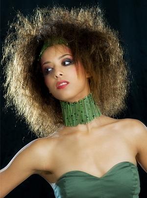 Kreatives Bambus Styling - Lächelndes Fotomodel im Styling mit Bambusschmuck an Hals und Kopf, wilden Haaren im Stil eines grossen Vogelnests, gekleidet mit einem passenden trägerlosen olivgrünen Top, fotografiert vor schwarzem Hintergrund.