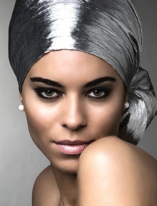 Beauty Shooting mit Dominique - Ein silbernes Kopftuch und Perlen als Ohrschmuck schmücken bei diesem Beauty Shot von Dominique, fotografiert über ihre nackte Schulter.