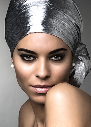 Test Shooting mit Dominique - Ein silbernes Kopftuch und Perlen als Ohrschmuck schmücken bei diesem Beauty Shot von Dominique, fotografiert über ihre nackte Schulter.