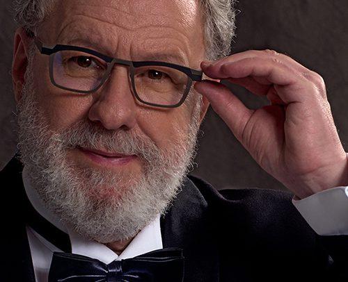 Künstler Frank Mauk - Studio Portrait im Smoking vor einem dunkel-braunen Hintergrund. Mit der linken Hand setzt er seine Brille zurecht.