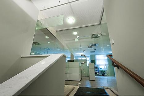 Firmenportrait Arztpraxis Dr. Med. Suso Lederle -Der gläserne Eingangsbereich der Arztpraxis, fotografiert vom Treppenhaus mit Blick in die Räume.