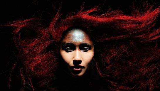 Rotschopf und Spezial MakeUp - Portrait von Fotomodel Diana mit roten wilden Haaren und Kriegsbemalung vor schwarzem Hintergrund.