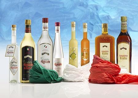 Getränke - Produkt Foto von 8 Flaschen feiner italienischer Spirituosen nebeneinander aufgestellt und teilweise mit Seidenpapier - grün, weiss und rot - umwickelt. Im Hintergrund unscharfes, blaues geknülltes Seidenpapier.