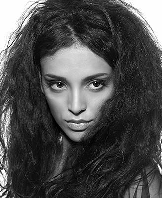 Schwarzweiss Beauty von Tina. Die vollen, lockigen Haare umgeben das ganze Gesicht und der Blick des gesenkten Kopfes geht zur Seite.