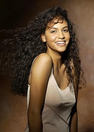 Sedcard Porträts von Selma, eine lachende Naturschönheit, ungeschminkt mit langen lockigen dunklen Haaren.