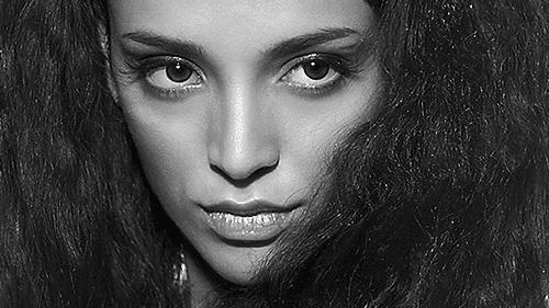 Schwarzweiss Portraits von Nina Die vollen, lockigen Haare umgeben das ganze Gesicht und der Blick des gesenkten Kopfes geht zur Seite.