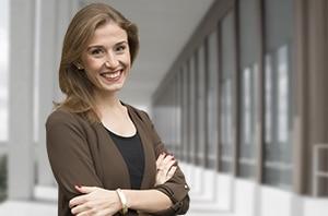 Ein Bewerbungsbild einer attraktiven lächelnden blonden Frau mit verschränkten Armen vor einem virtuellen Gebäude.