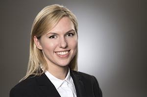 Eine junge freundlich lächelnde Frau mit langen blonden Haaren im Blazer mit weisser Bluse vor einem montierten imaginären Hintergrund..