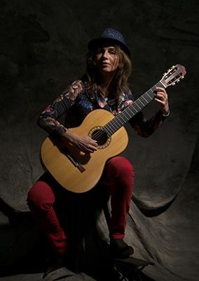 Eine Porträtfotografie der Künstlerin Julia Scheuffele mit ihrer akustischen Gitarre. Sie führt ein klassisches Stück vor.