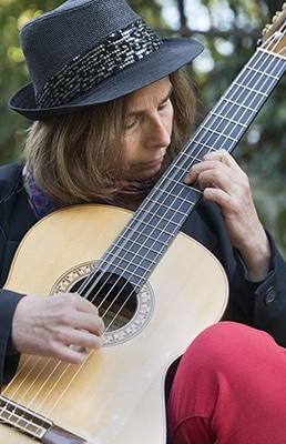 Die Künstlerin Julia Guitar Scheuffele konzentriert sich auf ihre akustische Gitarre und führt ein klassisches Stück vor.