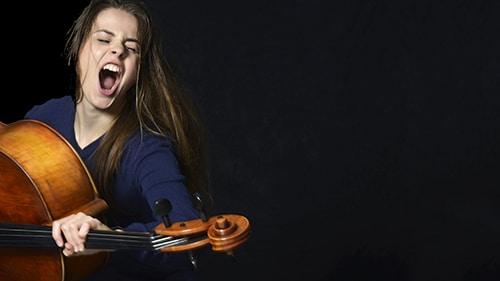 Junge Cellistin mit ihrem Instrument in extatischer action.