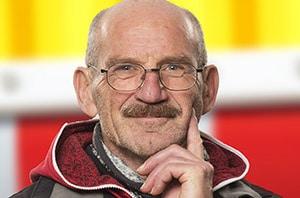 Portrait eines freundlich lächelnden Mannes in Denkerpose, mit Schnauzer und Brille vor einer gelb-roten Strassen Absperrung. alt attr für Portraitfoto,