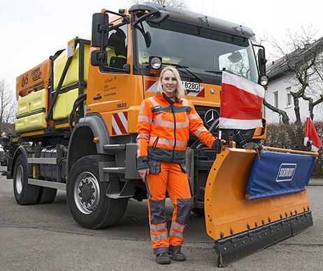 Eine junge blonde Frau steht stolz vor einem Spezialfahrzeug, einem Streuwagen mit Schneepflug, der AWS - Bild Alt-Attribute für Werbefotograf aus Stuttgart, Werbung,Wertstoffmobil,Ausbildungsberufe