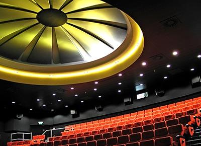 Architektur Fotografie Beitragsbild - ein altes Lichtspielhaus in Stuttgart mit roten, aufsteigenden Sitzreihen und einem riesigen, stilisierten, gelblich beleuchteten Ablüfter an der Decke. Corporate Photographer