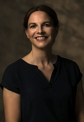 Stimmungsvolles Portrait einer lächelnden Frau mit nach hinten zusammen gebundenen Haaren im kurzärmligen schwarzen Top. alt attr. für Julia Hofelich Portraits, NEBELJAGD, TOTWASSER