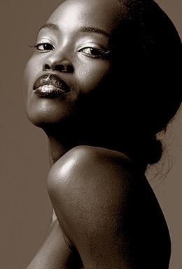 Getontes Schwarzweiss Portrait einer stolzen Afrikanerin. Seitlich fotografiert von unten über die nackte Schulter. Sie hat hochgesteckte Haare, einen herablassenden Blick und hochgesteckte Haare.