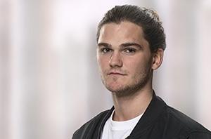 Portraitfotografie eines jungen Mannes mit Dutt mit unscharfem künstlichem Hintergrund