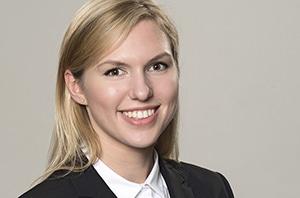 Bewerbungsfoto einer jungen strahlenden Blondine mit langen Haaren im Business Stil.