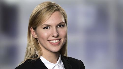Eine junge freundlich lächelnde Frau mit langen blonden Haaren im Blazer mit weisser Bluse vor einem montierten imaginären Hintergrund.. Fotograf in Stuttgart Ost