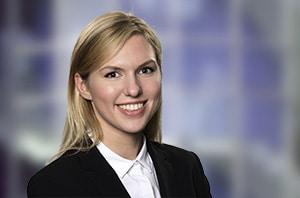 Eine junge freundlich lächelnde Frau mit langen blonden Haaren im Blazer mit weisser Bluse vor einem montierten imaginären Hintergrund. Portraitfoto in Stuttgart Ost
