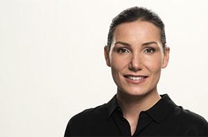 Bewerbungsfoto einer jungen lächelnden Frau im Querformat - ihre Haare hat sie nach hinten gebunden und sie trägt ein schwarzes Polo-Shirt.