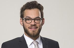 Ein Businessportrait für die Bewerbung eines jungen Mannes. Im klassischen Stil, fotografiert im Querformat vor grauem Hintergrund, mit Krawatte, weissem Hemd und Jacket.