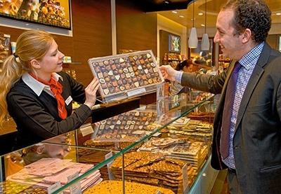 Die Verkäuferin in einer Chocolaterie präsentiert einem Kunden ein Schachtel Pralinen über den gläsernen, mit Schokoladen gefüllten, Verkaufstresen hinweg. alt attr. Firmenportrait Fotografie