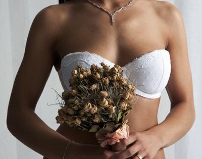 Dessous Detail von weissem BH, verwelktem Hochzeits-Blumenstrauß und einer Halskette im Anschnitt fotografiert mit weichem Licht vor weissem Hintergrund.