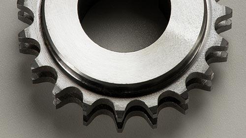 Nahaufnahme von einem Doppelzahnrad aus Edelstahl, mit Lichtreflexen, auf einer grauen Fläche liegend, fotografiert.