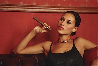 Eine rassige Brasilianerin mit einer Zigarre zwischen den Fingern vor einer roten Wand. alt attr. Editorial fotoshooting, Fotoshooting on location, Kreativshoot