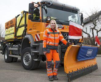 Eine junge blonde Frau steht stolz vor einem Spezialfahrzeug der AWS, einem Streuwagen mit Schneepflug. alt attr. für Werbe Fotografie, Unternehmenfotografie, Ausbildungsberufe
