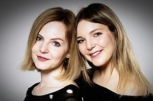 Portraitaufnahme im Studio von zwei blonden Schwestern, lächelnd und Kopf an Kopf gelehnt.