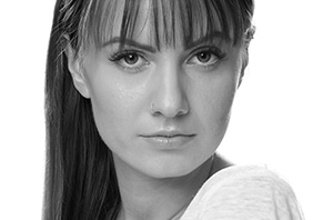 Portraitfoto - Schwarzweiss-Headshot Foto einer jungen attraktiven Frau mit langen Haaren und Ponyfrisur. alt attr für Paarfotos, Fotoshooting, Headshot, HeadshotFotografie, Portraitshooting