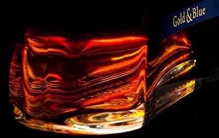 Highland Queen - Edler Whiskey und feurige Farbe - Makroaufnahme der feurigen Lichtspiele und Lichtbrechungen im Flaschenboden einer Whiskey-Flasche. Alt attrubute for Flaschen Fotografie Stuttgart,Produkt Fotografie Stuttgart,