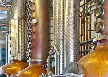 Destillerie der Schnapsbrennerei WEIS im Schwarzwald. Der Ausschnitt zeigt drei Brennkessel, viele Messgeräte, Kontrolleinrichtungen und Rohrleitungen. Image alt for Industriefotografie, Industriefotograf, Werbefotos, Unternehmen Fotografie