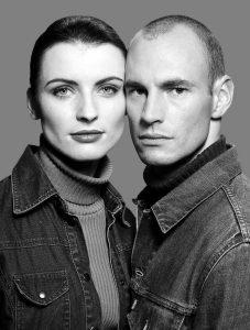 ein junges Paar, Bruder und Schwester, Wange an Wange in Rollkragenpullis und Jeansjacke. alt attr. für zufriedene Kunden