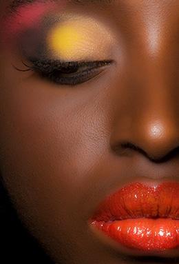 Kreatives Beauty Make Up auf dunkler Haut - Nahaufnahme eines stark geschminkten Gesichts, einer Frau mit geschlossenen Augen, gelbem Lidschatten und knallroten Lippen. alt attribute for: Kreative Fotografie