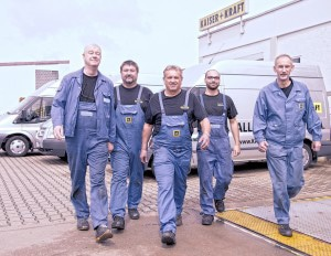 5 Kundendienst-Fachmänner im Blaumann schreiten im Freien vor der Firma auf die Kamera zu.alt attr für Firmenportrait, KaiserKraft Versandhandel
