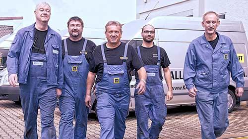4 Kundendienst-Fachmänner im Blaumann schreiten auf die Kamera zu.