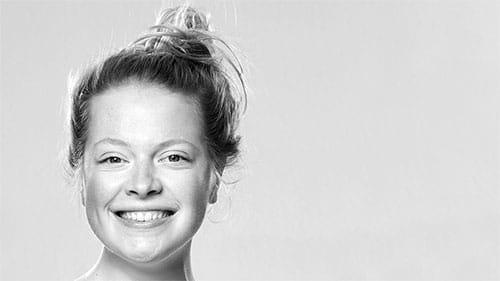 Beitragsfoto zu Bewerbungsfotos - Schwarzweiss Studio Porträt der jungen und fröhlichen Schauspielerin Marlene Hofmann mit Dutt vor hellem Hintergrund.