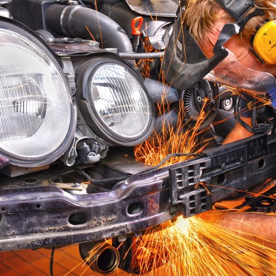 Ein Automechaniker in Schutzkleidung bei Mercedes Benz im Werk Untertürkheim erzeugt beim flexen an der Karosserie heftigen Funkenschlag. alt attribute: Corporate Fotografie Stuttgart, Foodfotografie