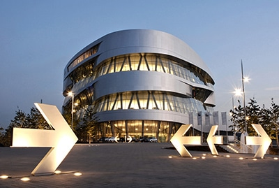 Mercedes Benz Museum Stuttgart in der Dämmerung mit beleuchteten Pfeilen zur Wegführung
