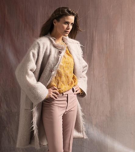 Modefotografie mit Model in Mantel, Bluse und Hose, massgeschneidert von Charlotte Jockers, vor einem gefärbten Stoff, für das Magazin