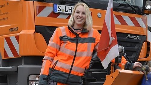eine junge blonde LKW-Fahrerin der AWS steht solz und lächelnd vor ihrem Räumfahrzeug, gekleidet in oranger Arbeitskleidung.