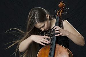 Eine junge Cellistin mit langen, wehenden Haaren zupft konzentriert die Saiten ihres Instruments. alt attr für Promis, Fotoshooting,