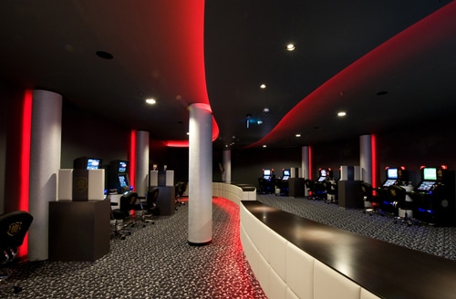 Innenaufnahme eines Spiel Casinos in Stuttgart mit stimmungsvoller, indirekter roter Beleuchtung. Rechts und links an der Wand stehen Spielautomaten, in der Mitte geteilt durch einen geschwungenen Tresen.